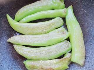 虎皮青椒,小火慢炕,一边炕一边用勺子按压青椒,炕的时候要经常翻动青椒,避免青椒单面炕糊,部分青椒已起虎皮,要将没有起虎皮的青椒炕到。当虎皮已起,青椒已完全变软,盛出备用。