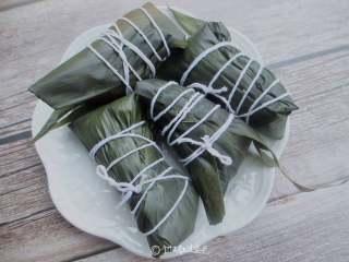 八宝蜜枣粽,把粽子盖上,用大拇指按住,包好后用绳捆起来
