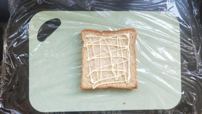 金枪鱼沙拉三明治,取一片吐司,我买的是全麦吐司,(底下铺上保鲜膜,)挤上沙拉酱。