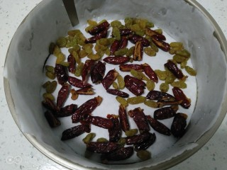 家庭版甑糕,模具铺上油纸,先铺一层枣和葡萄干。