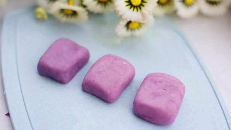 香甜软糯的奶香紫薯芝麻方饼,取小撮面团揉成小圆球然后捏成方块。