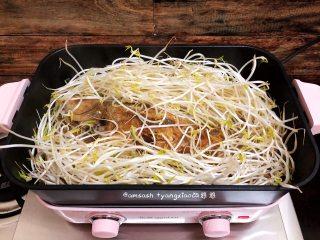 鲈鱼焖豆芽,水煮开时,把豆芽菜都倒入锅中,围在鲈鱼的周边