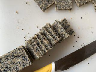 黑白芝麻酥块,冷冻好的面团取出,切成0.8cm左右的片,摆入烤盘。