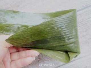 红糖红豆蜜枣粽,粽叶如果是细点的,就两片包一个,粗大的叶子一片包一个。叶子剪平根部,光滑面儿向上,从中间卷起成圆锥状