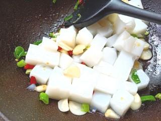 炒豌豆凉粉,倒入切好的凉粉,翻炒片刻