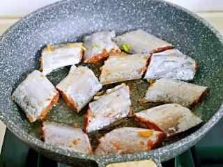 红烧带鱼,起油锅,将腌制好的带鱼段摆放在锅中。