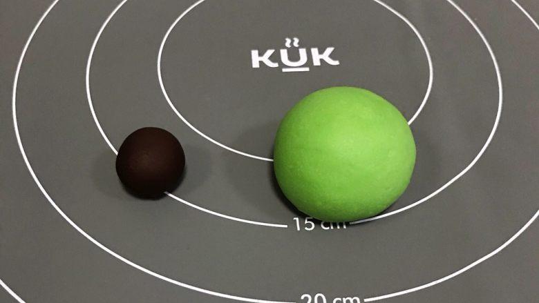粽子表情包馒头,把5克的小面团加<a style='color:red;display:inline-block;' href='/shicai/ 920'>可可粉</a>(竹炭粉)揉匀,35克的面团加抹茶粉和少许绿色色素揉匀。没有绿色色素可直接用抹茶粉或菠菜粉。