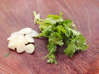 红油拌莴苣,大蒜去皮后,用刀切成薄片,香菜切段。