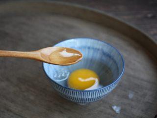 鹅蛋鸡肉炒蒜苔,一枚鹅蛋磕入碗中,放入1小勺的白糯米酒。