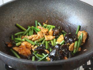鹅蛋鸡肉炒蒜苔,放入蒜苔和木耳,炒至蒜苔断生。