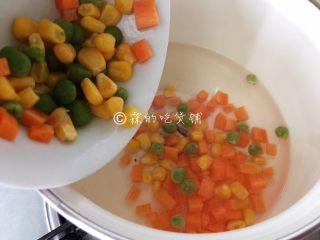 蛋包饭,烧一点点水,把胡萝卜丁和玉米、小豌豆一起,汆烫一下。