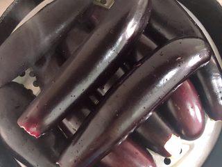 蒜香蒸茄子(泡椒蒜泥版),长茄子中间切开,放在蒸锅中,茄子心朝下摆放。