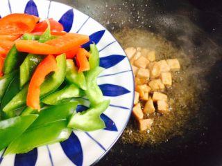 彩椒炒鸡丁,倒入青椒、红椒
