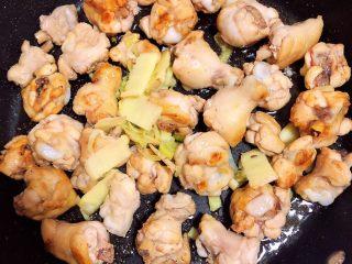 南瓜香菇鸡翅焖饭,放入鸡翅根翻炒均匀,再放入葱姜继续翻炒。