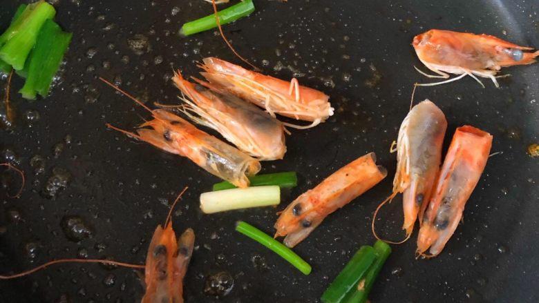 什锦虾仁粥,锅加少许油烧热,虾头和葱段放入翻炒出虾油