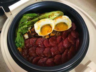 香肠焖饭,:放入青菜淋入酱汁摆上切开的咸鸭蛋,继续焖5分钟即可!