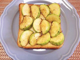 水波蛋西葫芦吐司,将煎好的西葫芦放在面包片上。