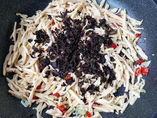 梅菜笋丝,将泡发洗净的梅干菜攥干水份后加入,翻炒均匀。