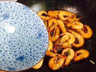 姜葱油爆大虾,淋入少许热水翻炒至熟