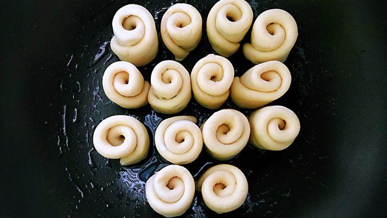 水煎绿豆玫瑰花馒头,平底不沾锅刷一层薄薄的油,切开一个,往平底锅中放一个,直到全部卷完切开全部放在平底锅中,盖上盖子,在锅中放的时候每一个玫瑰花馒头之间留点空隙出来,得发酵的。