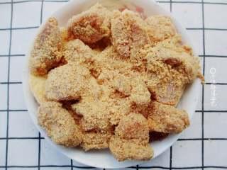 粉蒸排骨,把腌制好的肉排放在蒸肉粉里裹一圈,让蒸肉米粉能均匀的裹上排骨。拌好米粉的排骨均匀摆放在土豆的上层