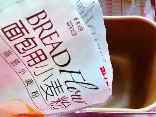 南瓜软麻花,接着将金龙鱼高筋面粉倒入面包机里,用高筋粉做软麻花,麻花的口感更有嚼劲,然后依次加入鸡蛋、南瓜泥、酵母、细砂糖和玉米油。
