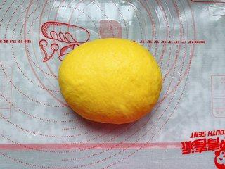 南瓜软麻花,取出发酵好的南瓜面团,撒上少许面粉揉光滑。