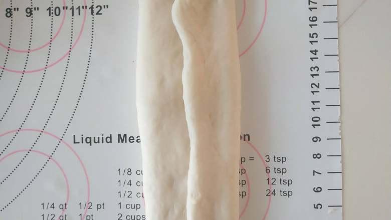 优格蜂蜜吐司,7、取出一个面团擀成椭圆形,翻面后将两边向中间对折。 从上到下卷起。收紧底边。