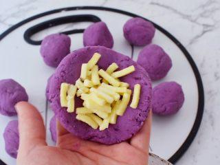 紫薯芝士饼,取一份面团按扁放入芝士碎