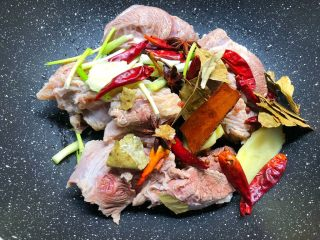 卤牛肉,把冲洗干净的牛腱放入锅里,加入剩下的葱段和姜片,再加入桂皮、八角、花椒、香叶。