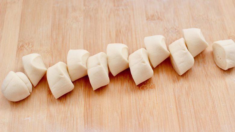 西葫芦猪肉发面包,把醒发好的面团,排气揉匀后、搓成长条,用刀切成大小一致的剂子。