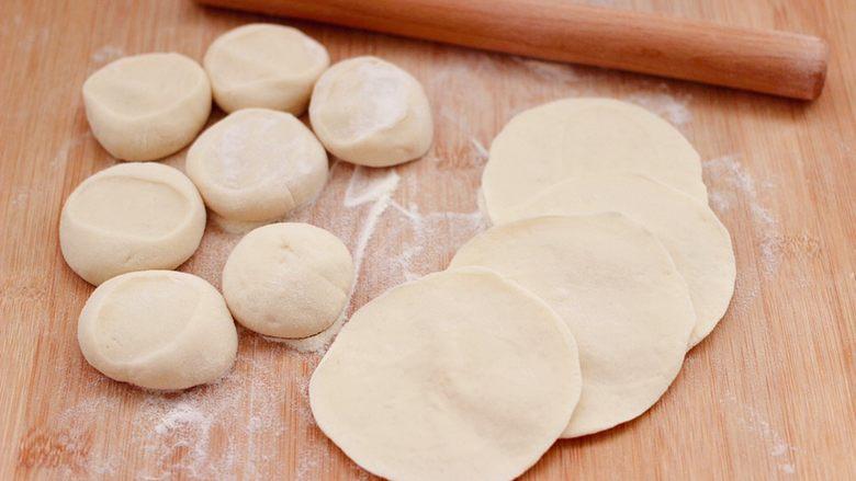 西葫芦猪肉发面包,摁扁后,用擀面杖擀成圆形薄面皮。