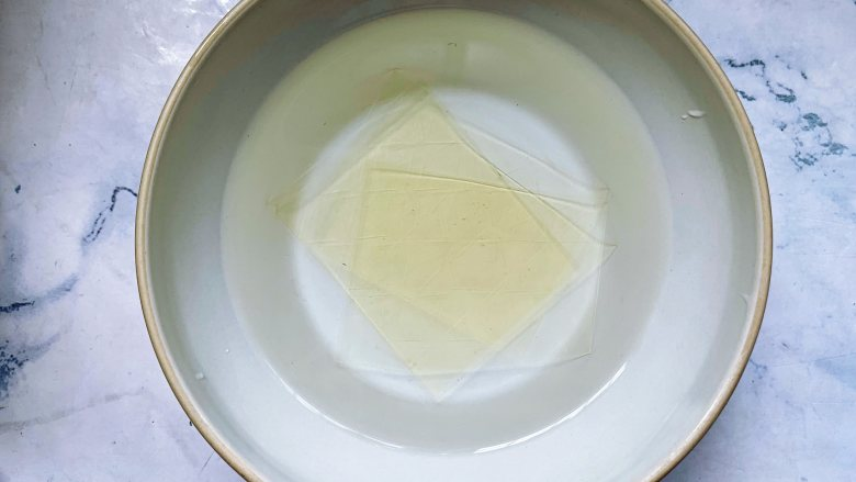 焦糖双色咖啡奶冻,首先将1片吉利丁片用冰水泡软,大概浸泡15分钟的时间。