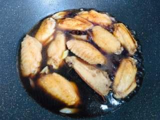 红烧鸡翅,继续往锅里倒入开水,水量以没过鸡翅表面为准。把八角和桂皮一起加入锅中,转到大火,将汤汁烧开。