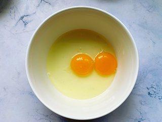 黑芝麻薄饼,碗里敲入2个鸡蛋。