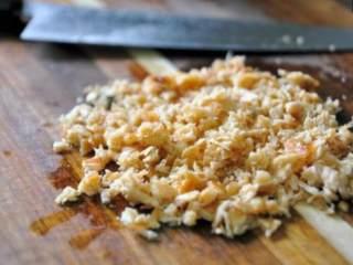 鮭鱼炒饭 ,将拨散的鮭鱼取出切碎(若在不沾锅内用利物捣碎会破坏涂层),鮭鱼碎的越均匀、大小与米饭越一致口感越好