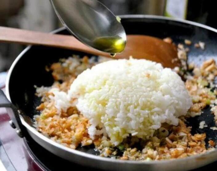 鮭鱼炒饭 ,在锅内下一碗白饭,并在白饭上均匀淋上 1.5 匙的食用油,轻轻将白饭拨鬆至锅子四周