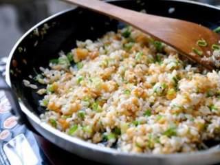 鮭鱼炒饭 ,倒入酱油并加入葱绿拌炒均匀,这个阶段到起锅很快,酱油有湿润的功能,当炒饭不湿不乾的状态就可以起锅了,要留意如果炒的时间过久会开始黏饭,酱香味也没了