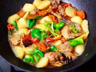 土鸡土豆粉条一锅炖,大火翻炒至青红辣椒,断手变色,撒上香菜段即可。