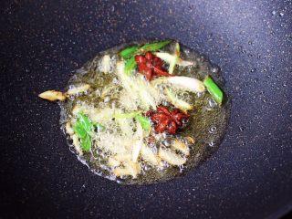 土鸡土豆粉条一锅炖,锅烧热后,倒入花生油烧至六成热时,放入八角小火慢慢炸香,再爆香葱姜丝。