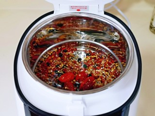 营养谷物杂粮粥,首先将泡好的红豆与杂粮倒入饭煲内胆中。