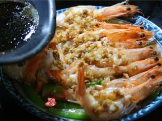 蒜蓉丝瓜蒸海虾,再次烧开炒锅,倒入少许食用油,一汤匙酱油,煮沸,淋在蒜蓉虾上面;