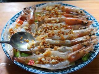 蒜蓉丝瓜蒸海虾,将混合炒香的蒜蓉酱油用汤匙舀起,均匀铺在海虾上面;
