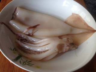 鱿鱼包饭,将鱿鱼外层红膜撕去,然后冲洗干净