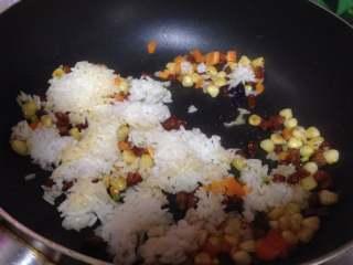 鱿鱼包饭,倒入米饭炒散、炒匀