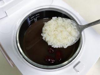 红豆薏米甜酒酿,炖煮剩余5分钟时候加入3~4勺的甜酒酿和2块冰糖或红糖。