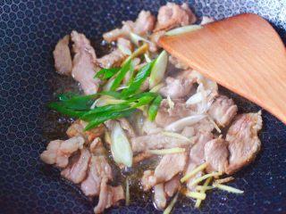 黄花菜炒肉片,大火继续翻炒片刻,加入葱姜炒出香味。