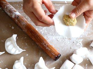 晶莹剔透的水晶饺,放入馅料,捏起一角,折一边和另外一边捏紧。