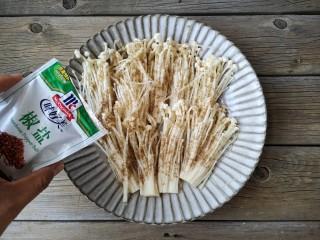 椒盐金针菇,将处理好的金针菇平铺在盘中,均匀撒上适量的椒盐,如果有时间可以腌制10分钟,没时间就接着进行下面的操作即可。