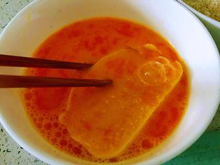 蒜香馒头片,鸡蛋打入碗中,放入一点点水,放入盐,用筷子搅开,用筷子夹起一个馒头片放入蛋液碗中,所有面全部粘上蛋液。
